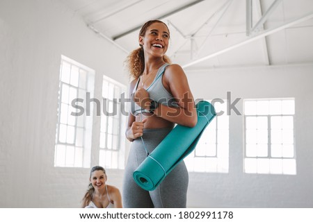 Smiling fitness woman standing in a fitness studio carrying a yoga mat. Portrait of a young woman at a fitness training centre.