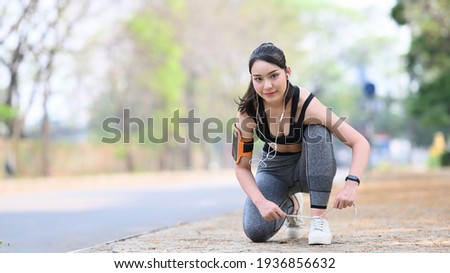 Smiling fitness woman tie shoelaces  getting ready for jogging outdoors. Сток-фото ©