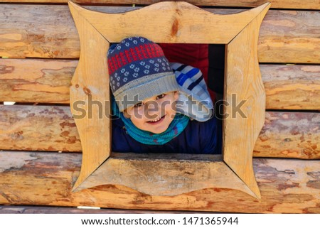smiling five-year-old boy boy looks out the window of the house. children's wooden house on the Playground outdoors #1471365944