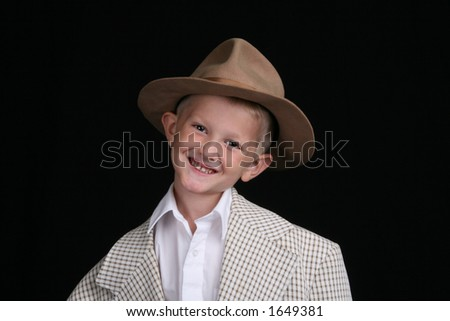 smiling five year old boy plays dress-up in oversized suit