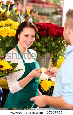 Smiling florist man customer buying flowers credit card shop
