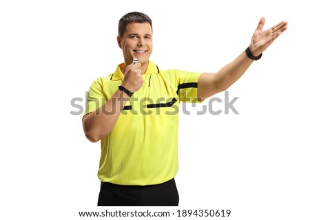 Smiling football referee blowing a whistle and pointing isolated on white background