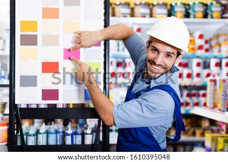 Smiling foreman in blue overalls showing samples of paint on stand in store