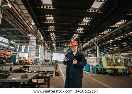 Smiling foreman in protective work wear using mobile phone at large metal industry hall.