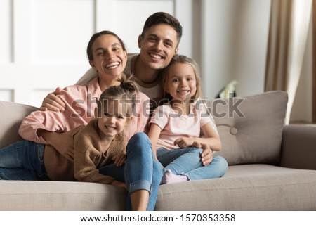 Smiling foster care parents hug small cute kids daughters relaxing on couch at modern home together, happy mother father and children siblings bonding posing for family portrait in cozy living room