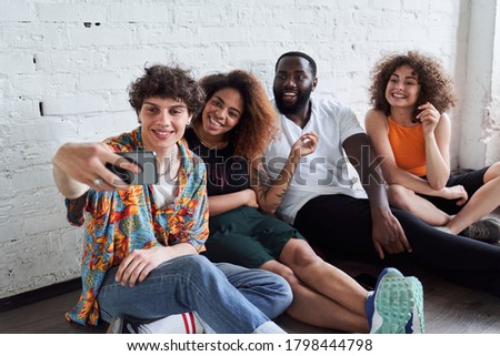 Smiling fouur friends taking selfie together while sitting on the floor near white wall Foto stock ©