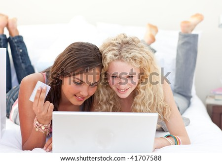 Smiling friend girls shopping online in a bedroom