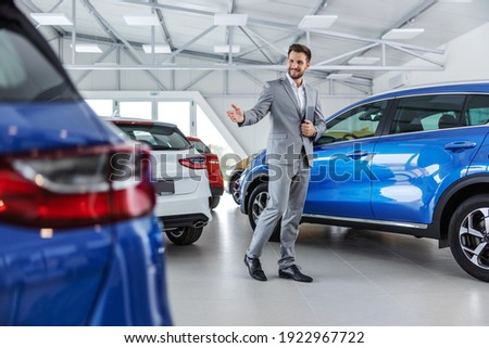 Smiling friendly car seller in suit walking around car salon and showing around cars.