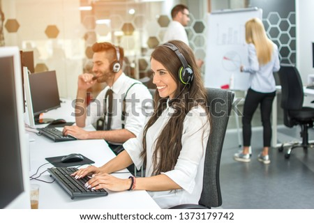 Smiling friendly female call-center agent with headset working on support hotline in the office