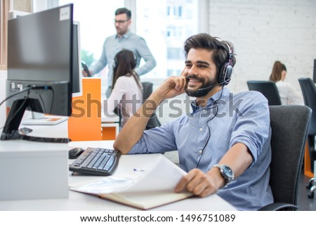 Smiling friendly helpline technical support agent talking with a client via hands-free headset.