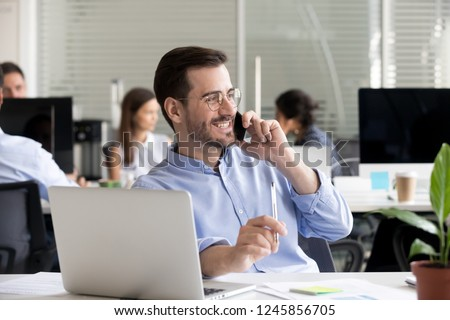Smiling friendly man talking on phone in office, having pleasant conversation with client or customer, receiving good news or offer, marketing manager making business call, chatting with friend