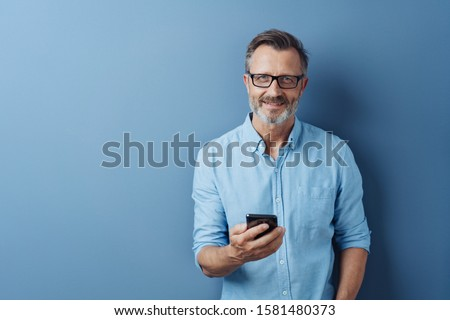 Smiling friendly man wearing glasses standing holding his mobile phone looking at the camera with a warm smile over a blue studio background with copy space Photo stock ©