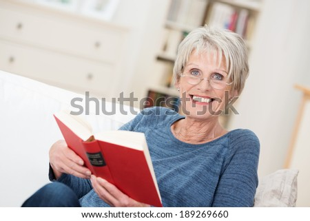 Smiling friendly senior woman sitting on a couch in her living room at home reading a book and looking up at the camera with a vivacious smile
