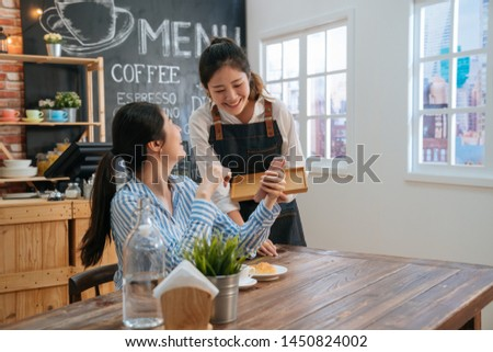 Smiling friendly waitress serving coffee drinks and croissant to friend at cafe table. cafeteria server and regular female visitors laughing together at funny joke on cellphone in modern coffeehouse.