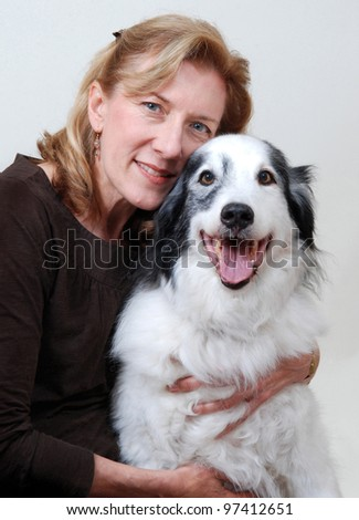 Smiling, friendly woman hugging dog