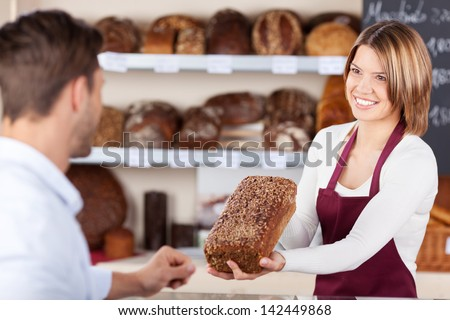 Smiling friendly young bakery assistant selling bread showing a wholewheat loaf to a male customer - stock photo