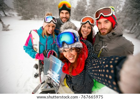 smiling friends having fun on winter hodays. Snowbarders and skiers group team friendship making selfie
