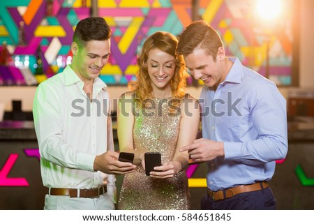 Smiling friends looking at mobile phone in bar