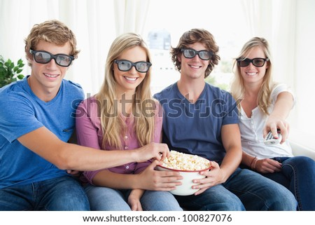 Smiling friends watching a funny movie in three dimension  as they all eat some popcorn - stock photo