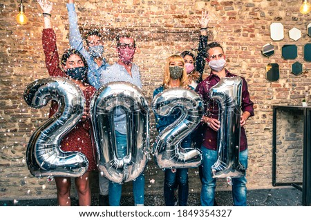 Smiling friends with face mask are celebrating new year's eve party in club in covid-19 time - Group of young people holding balloons looking at camera and smile wit eye all together throwing confetti