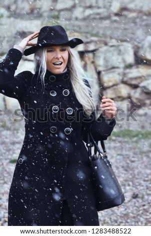 Smiling frozen woman dressed in black walking in the park on flying snowflakes background. Cold and windy weather season concept.