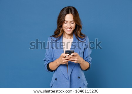 Smiling funny beautiful attractive young brunette woman 20s wearing basic jacket standing using mobile cell phone typing sms message isolated on bright blue colour wall background, studio portrait