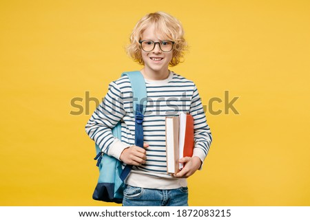 Smiling funny little male kid teen boy 10s years old wearing striped sweatshirt eyeglasses backpack holding school books isolated on yellow color background, child studio portrait. Education concept Stockfoto ©
