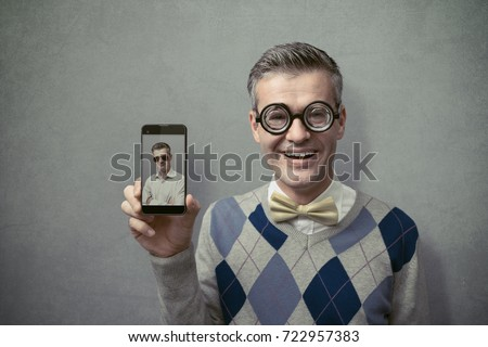 Smiling funny nerd guy with glasses showing his smartphone with blank screen, technology and communication concept