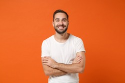Smiling funny young man in casual white t-shirt posing isolated on bright orange wall background, studio portrait. People sincere emotions lifestyle concept. Mock up copy space. Holding hands crossed