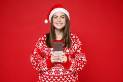 Smiling funny young Santa woman 20s wearing sweater Christmas hat hold chocolate bar looking camera isolated on bright red background studio portrait. Happy New Year celebration merry holiday concept