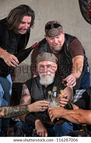 Smiling gang members toasting with bottle of liquor
