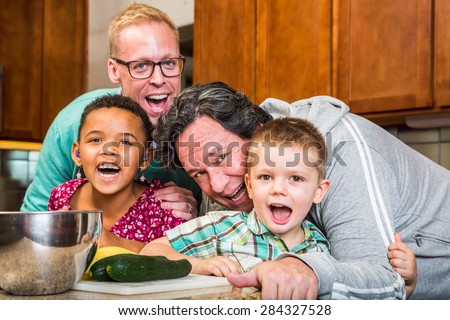 Smiling gay parents with their children in the kitchen