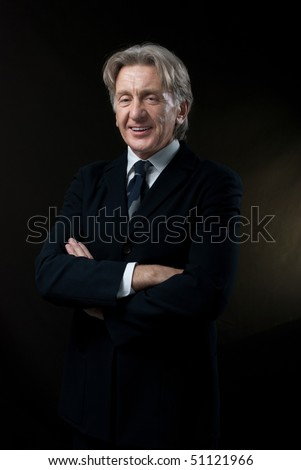 Smiling gentleman on dark background (Happy seniors lifestyle in studio uniform background series) - stock photo