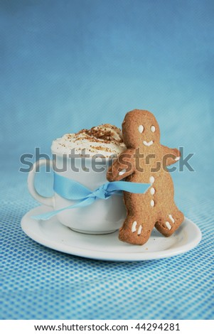 Smiling ginger bread man on a white hot chocolate cup