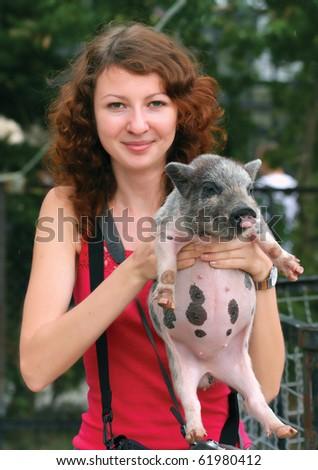 Smiling ginger girl holding piglet