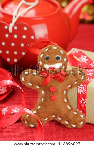 Smiling gingerbread man felt ornament with a Christmas gift tied with red ribbon