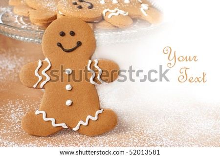 Smiling gingerbread man with additional cookies and dusting of confectioners sugar in background.  Macro with shallow dof and copy space.