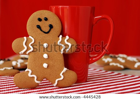 Smiling gingerbread man with red funnel mug. Additional cookies in soft focus in the background - stock photo