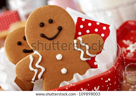 Smiling gingerbread men nestled in holiday dish with gift-wrapped surprise.  Baking ingredients and supplies (including baker's twine and rolling pin) in background.  Macro with extremely shallow dof. #109898003