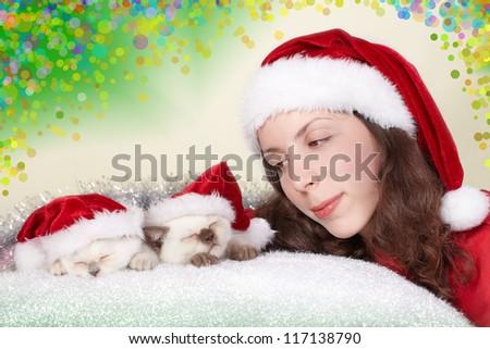 Smiling girl admires sleeping cats wearing Santa's hat