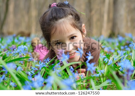 Smiling girl among the bluebells in the forest, blue spring flowers around