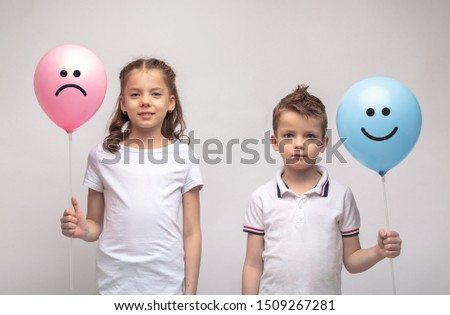 Smiling girl and boy closeup isolated on grey background . Image.  holding balls in their hands