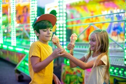 Smiling girl and boy eating ice cream in Funfair Park lights carnival