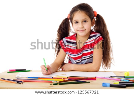 Smiling girl at the table drawing in the notebook, isolated on white
