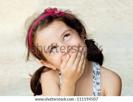 Smiling girl closing her mouth with her hand
