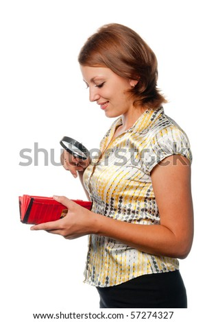Smiling girl considers a purse through a magnifier