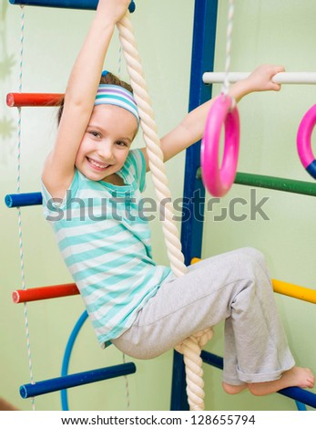 smiling girl doing sports gymnastics at home gym