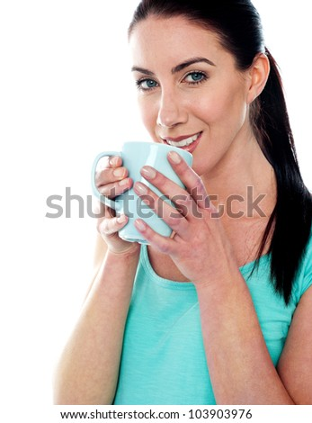 Smiling girl drinking coffee isolated over white