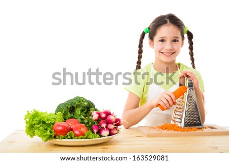 Smiling girl grate the carrots, cooking vegetables, isolated on white