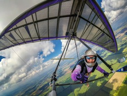 Smiling girl hang glider pilot shows thumb up while flying high over green fields below clouds. Wide angle selfie photo of extreme sport taken with action camera